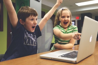 cheering kids by a computer