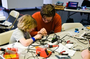 child soldering with teacher