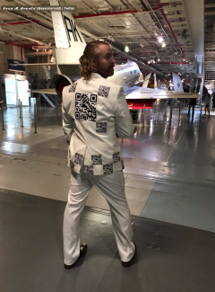 Rear view of a white suit covered in QR codes