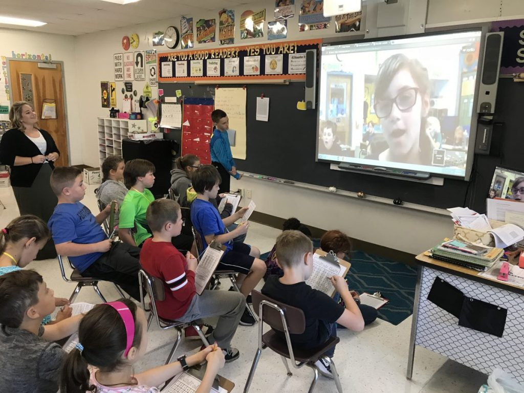 Classroom watching interactive display showing a Google Hangout with another class